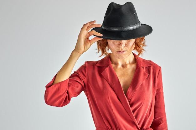 Mulher com cabelo curto ruivo natural e elegante chapéu preto olhando para baixo, com aparência e personalidade encantadoras