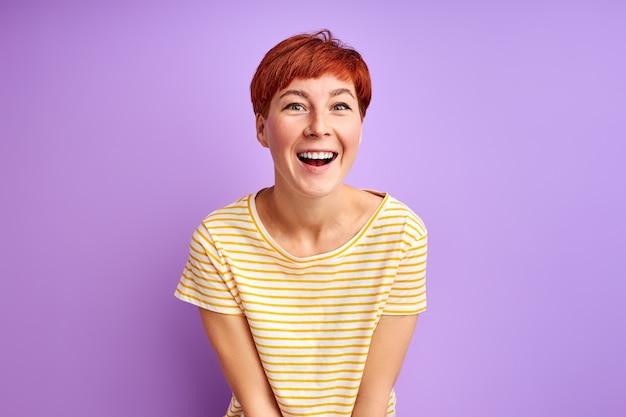 Mulher com cabelo curto ruivo se divertir, rir isolada na parede roxa, jovem mulher em roupas casuais, curtir a vida