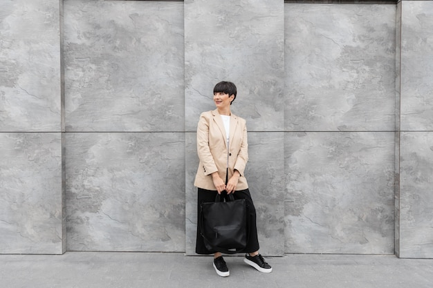 Mulher com cabelo curto segurando a bolsa