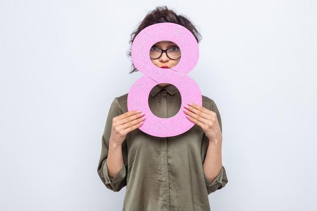 Mulher com cabelo curto segurando o número oito olhando este número em comemoração ao dia internacional da mulher, 8 de março