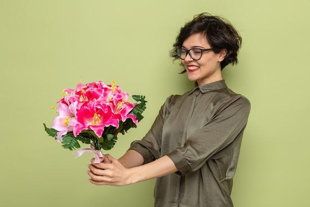 Mulher com cabelo curto segurando um buquê de flores olhando para flores feliz e satisfeita sorrindo alegremente comemorando o dia internacional da mulher, 8 de março, em pé sobre fundo verde