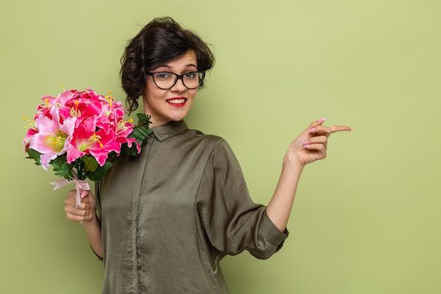 Mulher com cabelo curto segurando um buquê de flores sorrindo alegremente apontando com o dedo indicador
