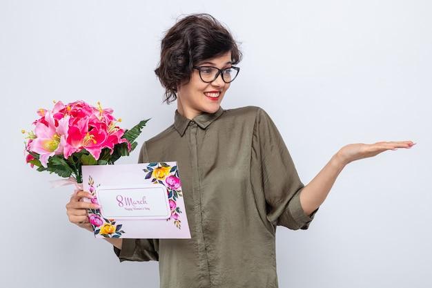 Mulher com cabelo curto segurando um cartão e um buquê de flores olhando de lado para o braço, apresentando algo com o braço, celebrando o dia internacional da mulher, 8 de março, em pé sobre um fundo branco