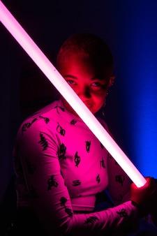Mulher com cabelo curto segurando uma luz de néon