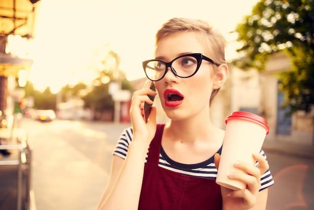 Mulher com cabelo curto, xícara de café com óculos falando ao telefone