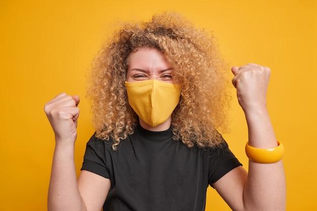 Mulher com cabelo encaracolado aperta os punhos com triunfo celebra o sucesso usa máscara protetora contra poses de camiseta preta de coronavírus contra fundo amarelo. manter medições de quarentena