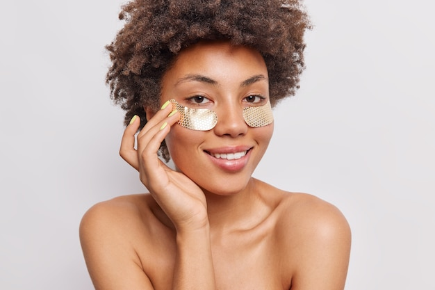 Mulher com cabelo encaracolado aplica adesivos de hidrogel de beleza sob os olhos sorri suavemente fica de topless em branco