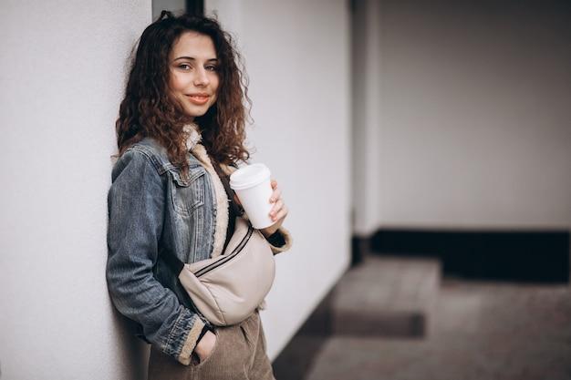 Mulher com cabelo encaracolado, bebendo café
