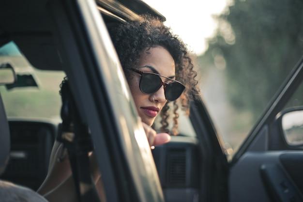 Mulher com cabelo encaracolado e óculos escuros olhando para fora do carro