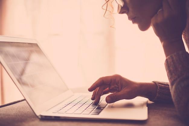 Mulher com cabelo encaracolado e óculos trabalhando com um laptop sentada confortavelmente no sofá em casa