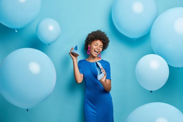 Mulher com cabelo encaracolado mantém os sapatos perto da boca finge cantar e usa vestido escolhe roupa para evento de festa isolado no azul