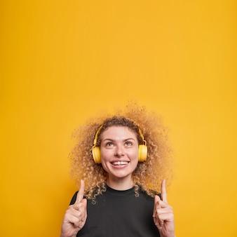 Mulher com cabelo encaracolado natural sorri positivamente mostra os pontos brancos dos dentes acima com os dedos indicadores tem expressão alegre ouve música através de poses de fones de ouvido sem fio