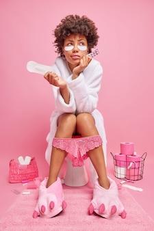 Mulher com cabelo encaracolado pensando profundamente tem menstruação sofre de cãibras menstruais segura analgésicos e absorvente higiênico usa roupão branco aplica adesivos