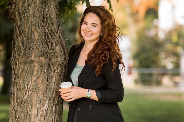 Mulher com cabelo encaracolado posando ao lado de uma árvore
