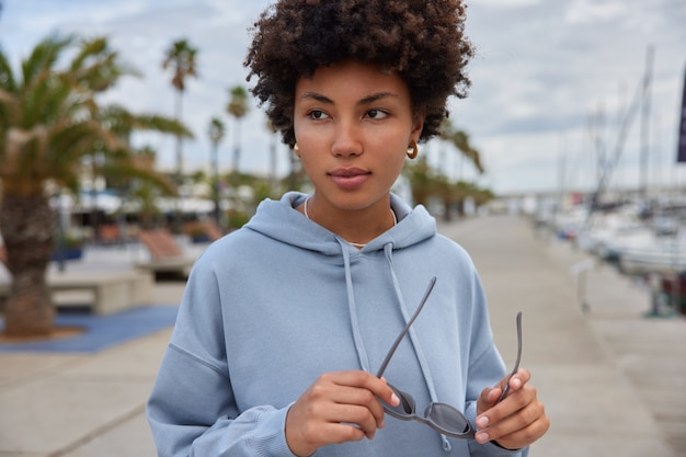 Mulher com cabelo encaracolado segura óculos de sol com capuz caminha perto do porto marítimo durante o dia e passa ativamente os fins de semana