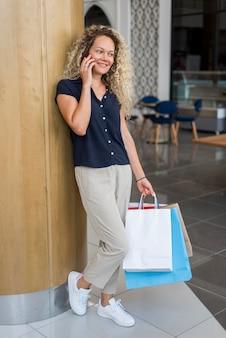 Mulher com cabelo encaracolado segurando sacolas de compras