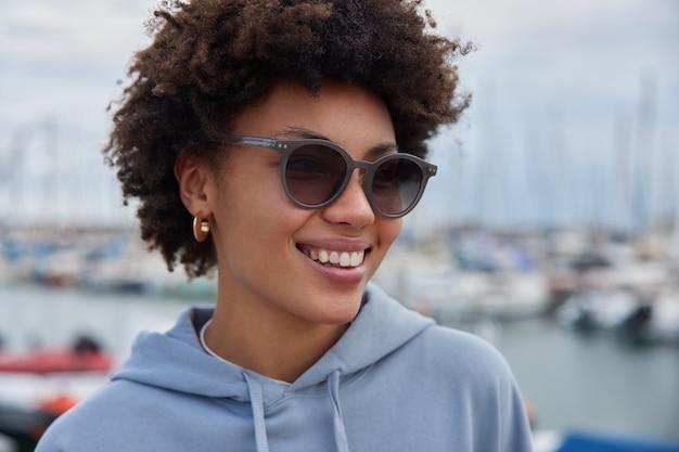 Mulher com cabelo encaracolado usa óculos escuros e moletom parece feliz, longe posa passeios no porto e admira a vista do mar