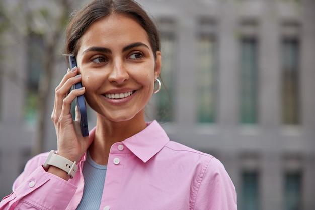 Mulher com cabelo escuro gosta de uma conversa no celular enquanto caminha ao ar livre usa uma camisa rosa casual, sorri suavemente e se sente feliz desfocada
