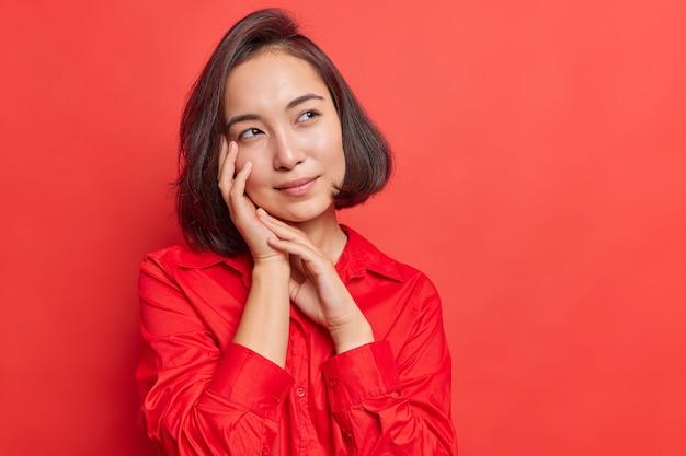 Mulher com cabelo escuro mantém as mãos perto do rosto tem expressão pensativa imagina algo em mente usa camisa vermelha em um tom com