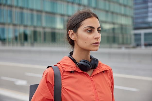 Mulher com cabelo escuro penteado parece pensativo ao longe usa blusão de couro carregada karemat para treinamento usa fones de ouvido estéreo para ouvir música durante o treino