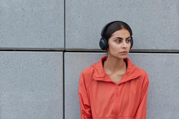 Mulher com cabelo escuro vestida com um anoraque casual desvia o olhar e escuta música com fones de ouvido sem fio poses contra uma parede cinza espaço em branco ao ar livre para sua informação