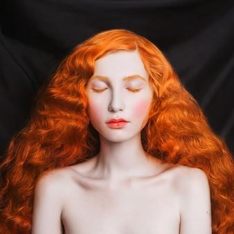 Mulher com cabelo esvoaçante vermelho longo encaracolado em um fundo preto. garota ruiva com pele pálida, olhos azuis, aparência incomum brilhante sem maquiagem. beleza natural. a menina da época do renascimento