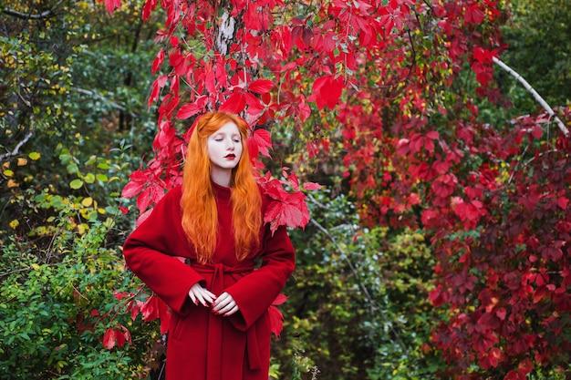 Mulher com cabelo liso vermelho com um casaco vermelho sobre um fundo brilhante de outono. garota ruiva com pele pálida e olhos azuis e uma aparência incomum brilhante com um anel no dedo e unhas vermelhas. estilo de rua