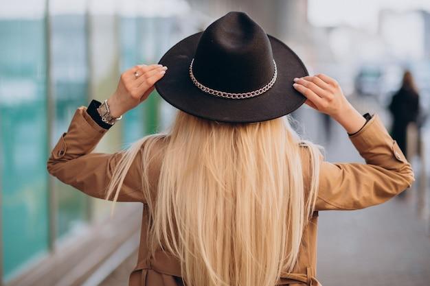 Mulher com cabelo loiro comprido em pé de costas