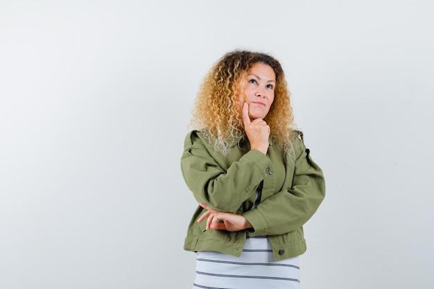 Mulher com cabelo loiro encaracolado, apoiando o queixo na mão na jaqueta verde e olhando pensativa, vista frontal.