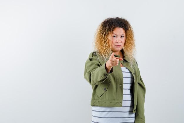 Mulher com cabelo loiro encaracolado, apontando na jaqueta verde e parecendo pensativa. vista frontal.