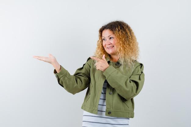 Mulher com cabelo loiro encaracolado, apontando para a palma da mão espalhada em uma jaqueta verde e olhando alegre, vista frontal.