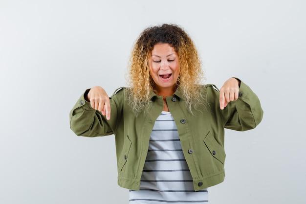 Mulher com cabelo loiro encaracolado apontando para baixo na jaqueta verde e parecendo curiosa. vista frontal.
