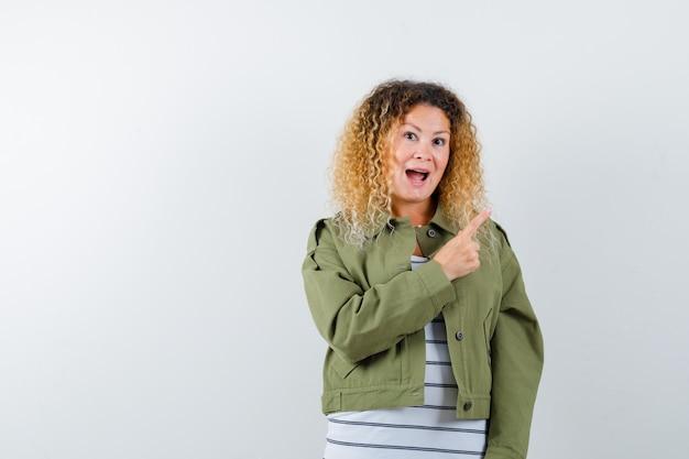 Mulher com cabelo loiro encaracolado, apontando para o canto superior direito com jaqueta verde e olhando feliz, vista frontal.