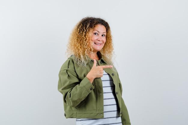 Mulher com cabelo loiro encaracolado, apontando para o lado direito com jaqueta verde e olhando alegre, vista frontal.