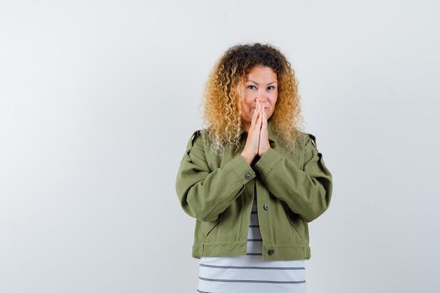 Mulher com cabelo loiro encaracolado com jaqueta verde, mantendo as mãos em gesto de oração e olhando esperançosa, vista frontal.