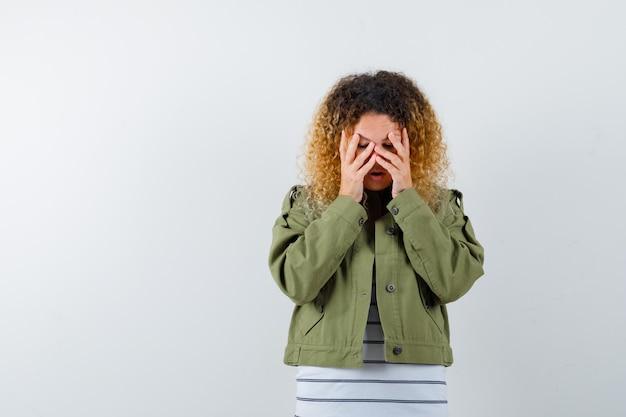 Mulher com cabelo loiro encaracolado com jaqueta verde, mantendo as mãos no rosto e parecendo chateada, vista frontal.