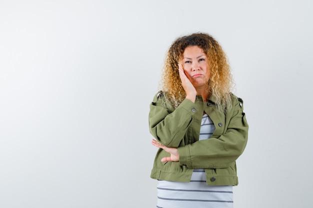 Mulher com cabelo loiro encaracolado, inclinando a bochecha por lado na jaqueta verde e olhando pensativa. vista frontal.