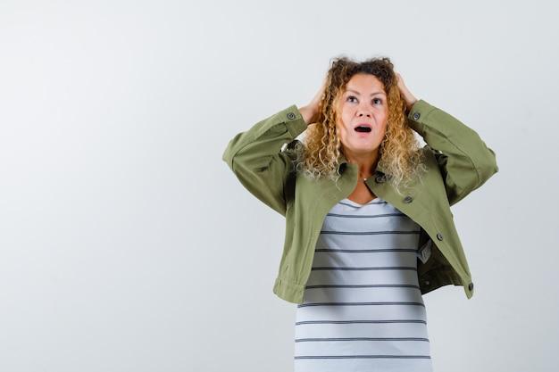 Mulher com cabelo loiro encaracolado, mantendo as mãos na cabeça com jaqueta verde e olhando pensativa, vista frontal.