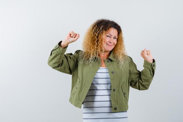 Mulher com cabelo loiro encaracolado, mostrando o gesto de vencedor com uma jaqueta verde e olhando alegre, vista frontal.