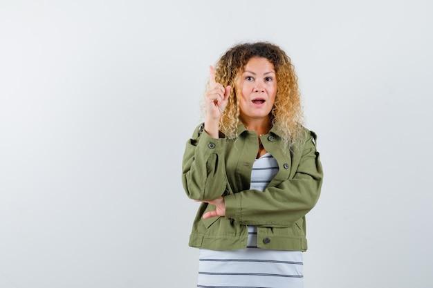 Mulher com cabelo loiro encaracolado, mostrando um gesto de eureka, apontando para cima com uma jaqueta verde e parecendo inteligente. vista frontal.
