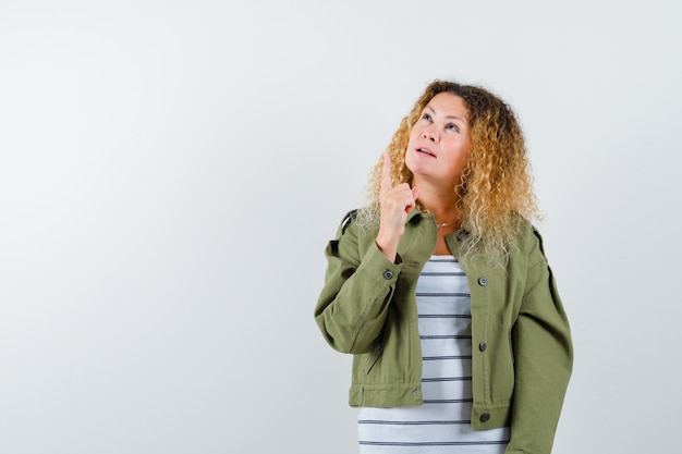 Mulher com cabelo loiro encaracolado na jaqueta verde, apontando para cima e olhando maravilhada, vista frontal.