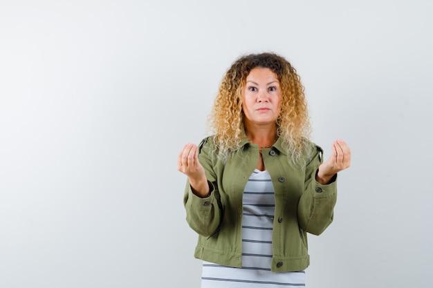 Mulher com cabelo loiro encaracolado na jaqueta verde, fazendo um gesto italiano e parecendo miserável, vista frontal.