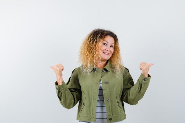 Mulher com cabelo loiro encaracolado numa jaqueta verde, apontando para as direções opostas com os polegares e olhando alegre, vista frontal.