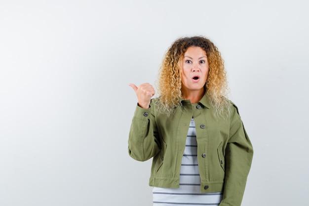 Mulher com cabelo loiro encaracolado numa jaqueta verde apontando para o lado com o polegar e olhando maravilhada, vista frontal.