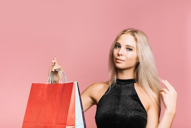 Mulher, com, cabelo loiro, segurando, bolsas para compras