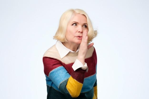 Mulher com cabelo loiro vestida dizendo notícias secretas sobre a travagem