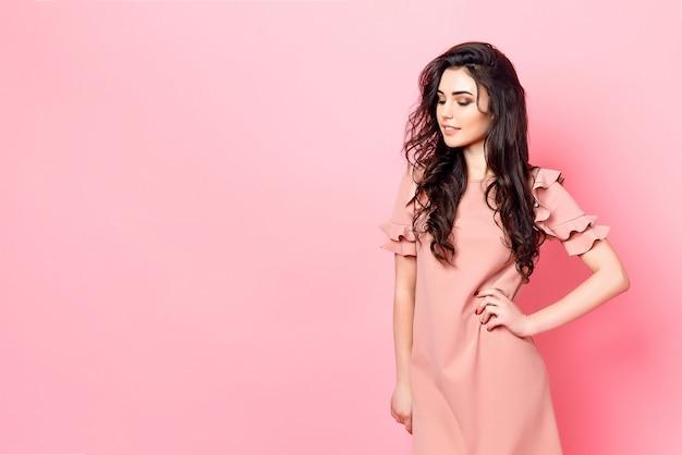 Mulher com cabelo longo cacheado em um vestido rosa.