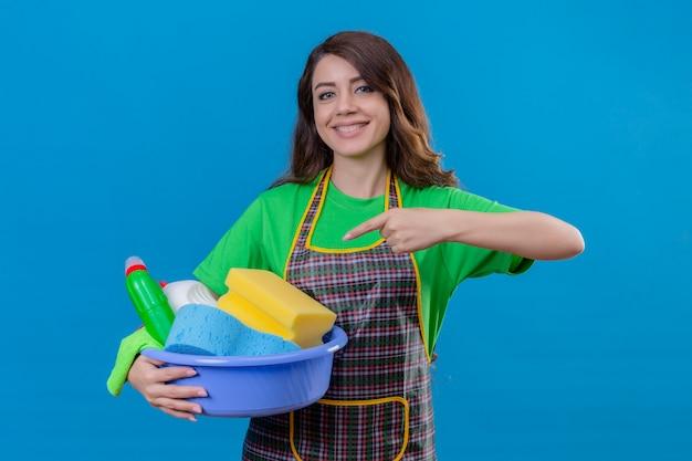Mulher com cabelo longo ondulado usando avental e luvas de borracha apontando com o dedo indicador para a bacia cheia de ferramentas de limpeza na mão sorrindo confiante em pé no azul