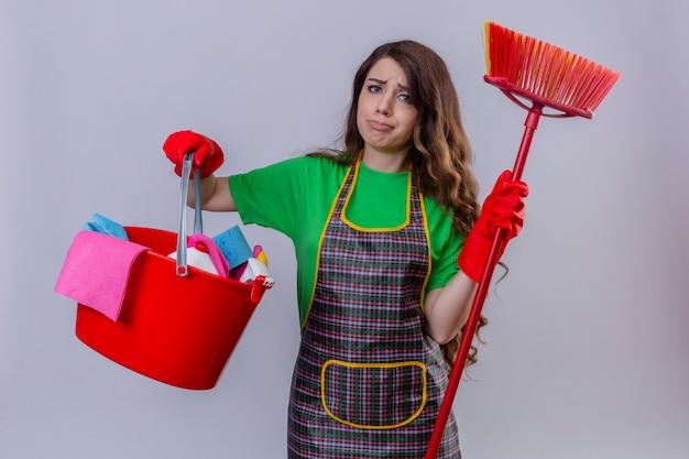 Mulher com cabelo longo ondulado usando avental e luvas de borracha segurando um balde com ferramentas de limpeza e esfregão parecendo triste e trabalhando com uma cara infeliz em pé