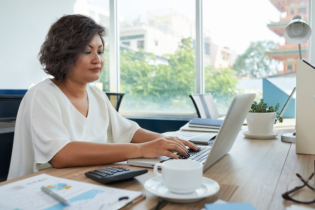 Mulher com cabelo ondulado curto, sentado na mesa no escritório e trabalhando no laptop
